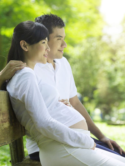 Pregnant Woman With Husband Sitting On Bench Against Tree