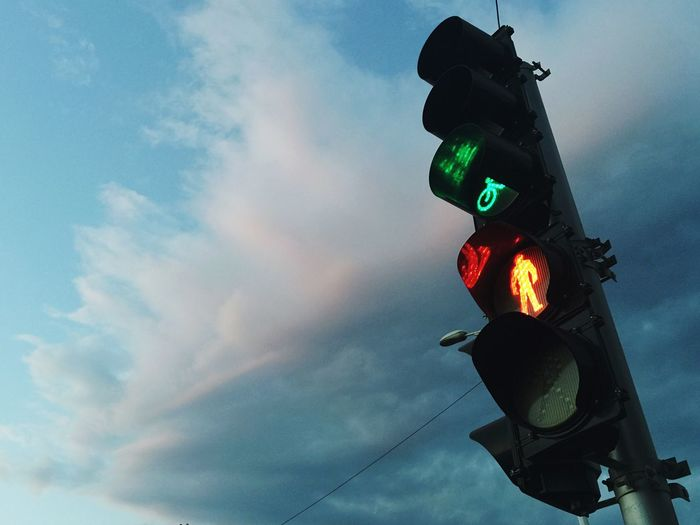 Low angle view of road signal against cloudy sky at dusk