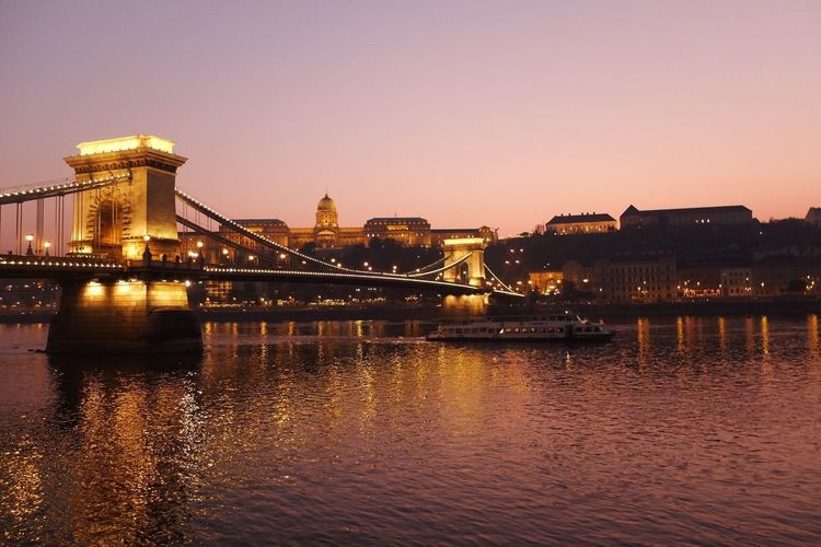 Illuminated bridge over river with buildings in background