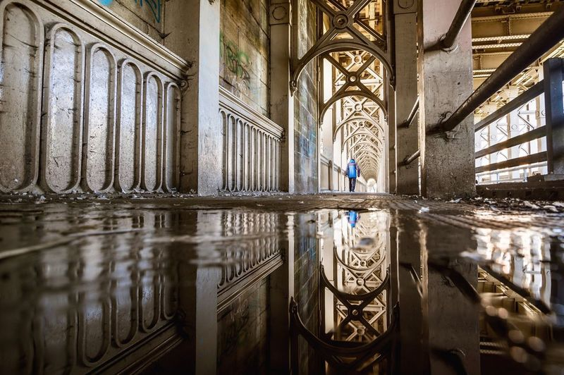 Reflection Of Man On Puddle In Building