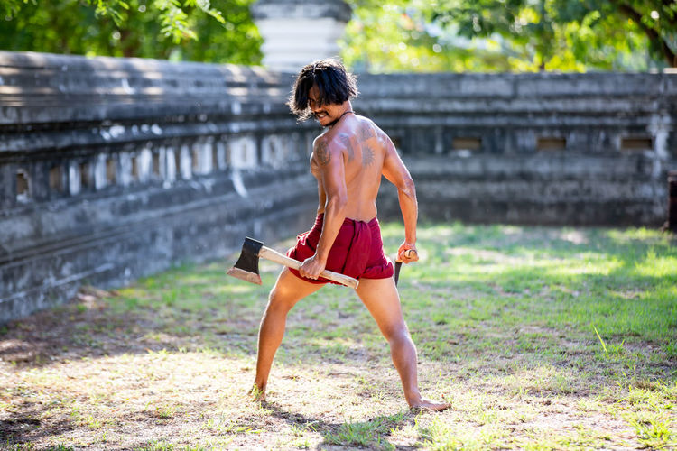 Full length rear view of shirtless man