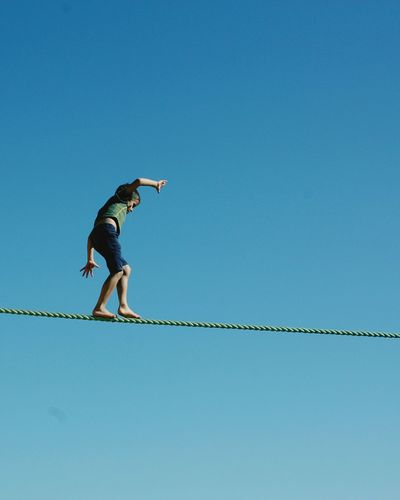Low Angle View Of Boy Walking On Rope Against Clear Blue Sky During Sunny Day