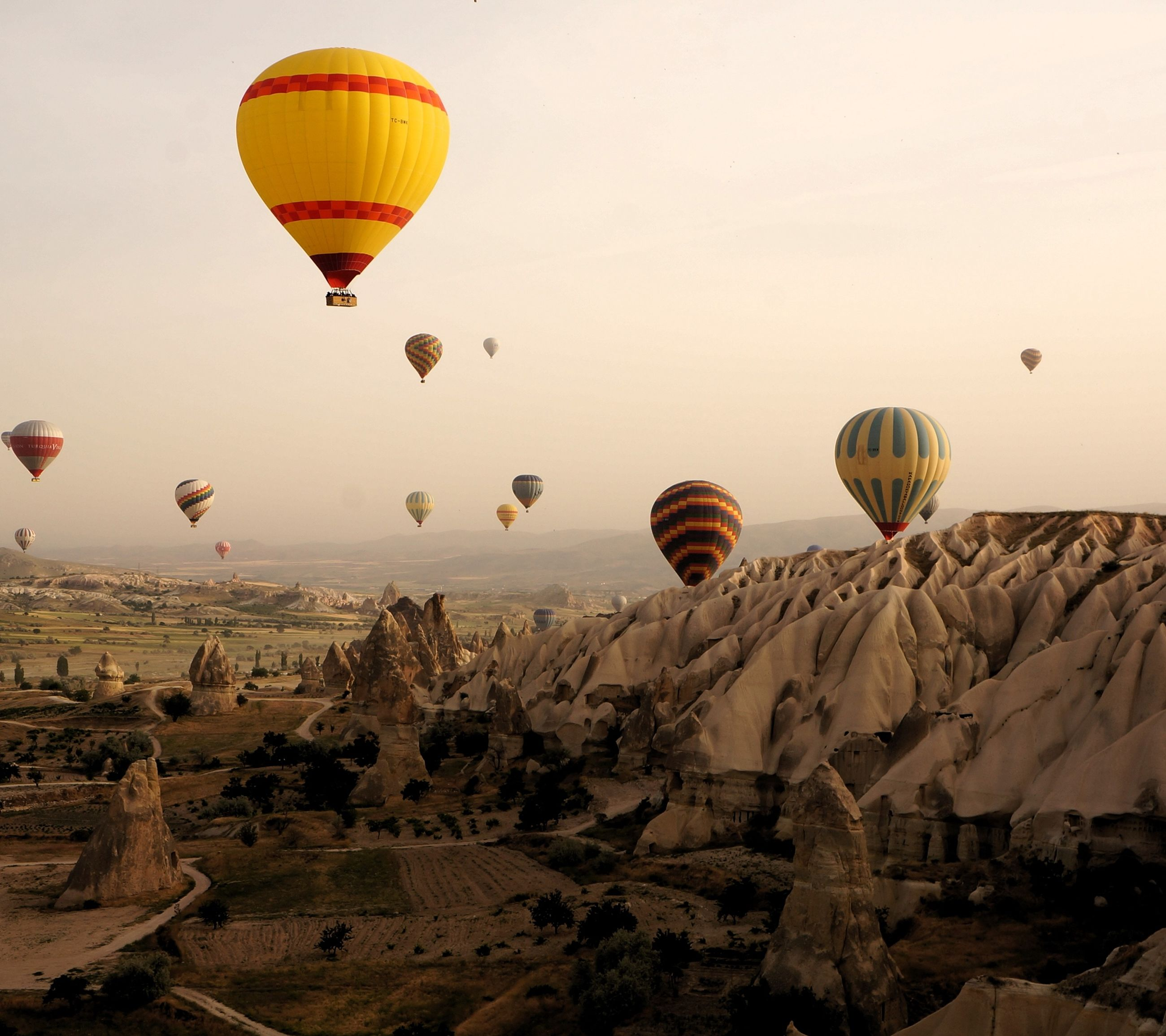 flying, hot air balloon, mid-air, parachute, sky, clear sky, paragliding, low angle view, scenics, adventure, tranquility, tranquil scene, multi colored, nature, copy space, beauty in nature, leisure activity, rock - object, outdoors, landscape