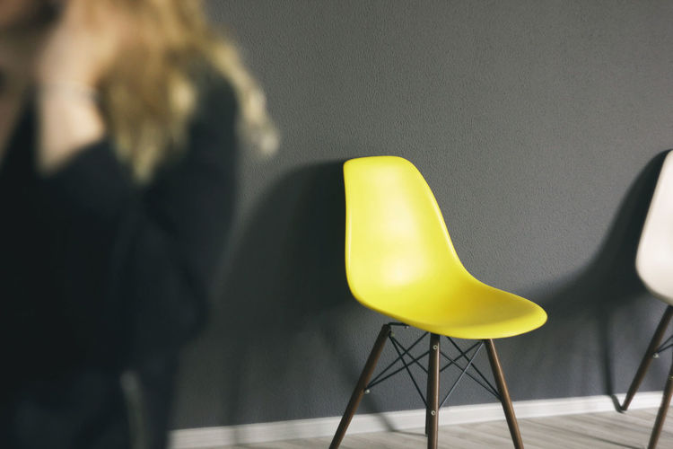 Empty yellow chair against black wall