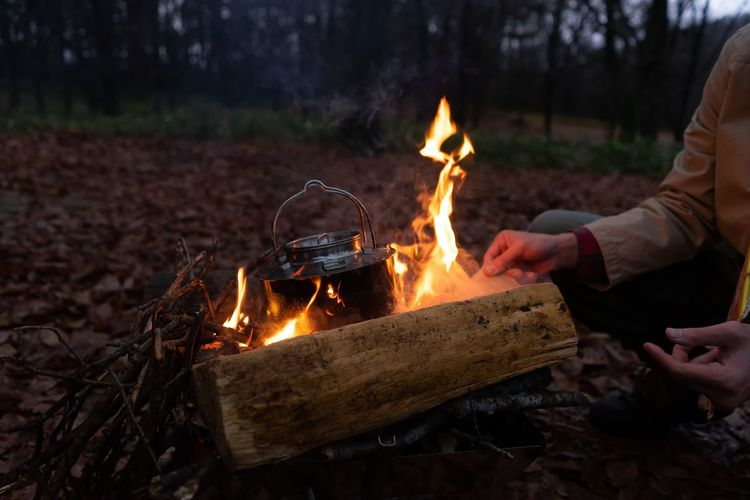 Low section of woman preparing tea on bonfire in forest