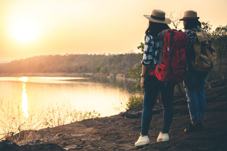 Two People Nature Sunset Sky Beauty In Nature Outdoors Landscape Travel Backpack Backpacker Women Sunlight Leisure Activity Real People Water Rear View Lifestyles Hat People Scenics - Nature