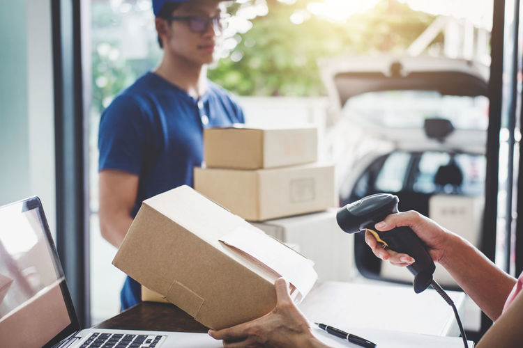 Cropped hands of woman scanning box with delivery man