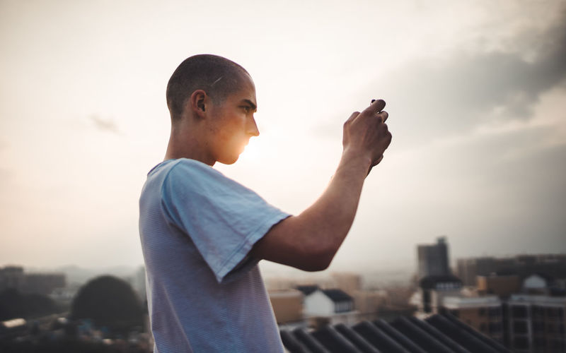 Man holding camera against sky in city