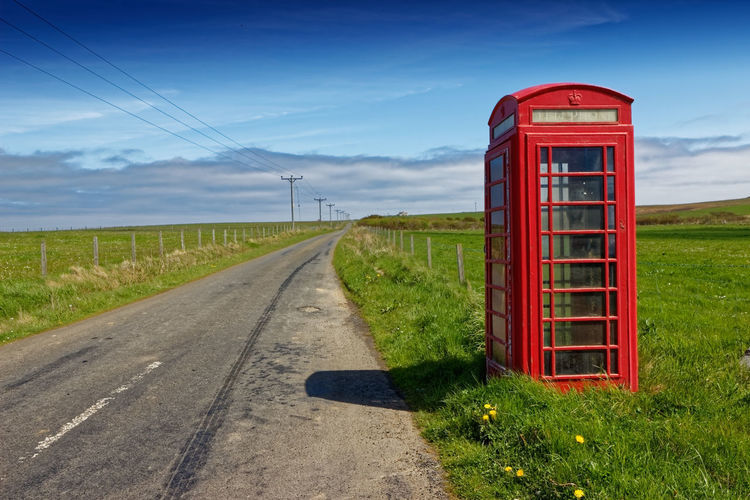 Telephone booth by empty road against sky