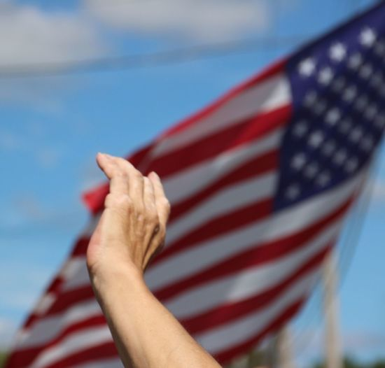 Cropped hand by american flag