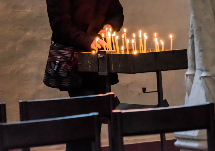 Midsection of man placing illuminated candle at church