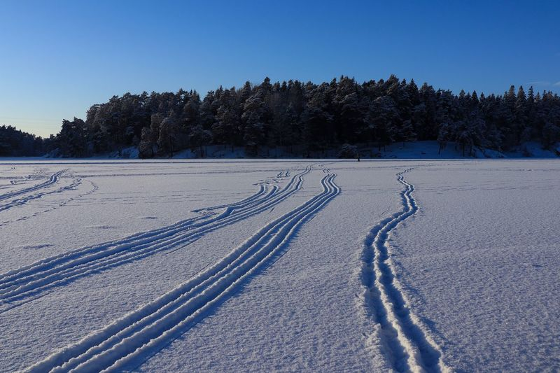 Tire tracks on snow covered field against clear sky