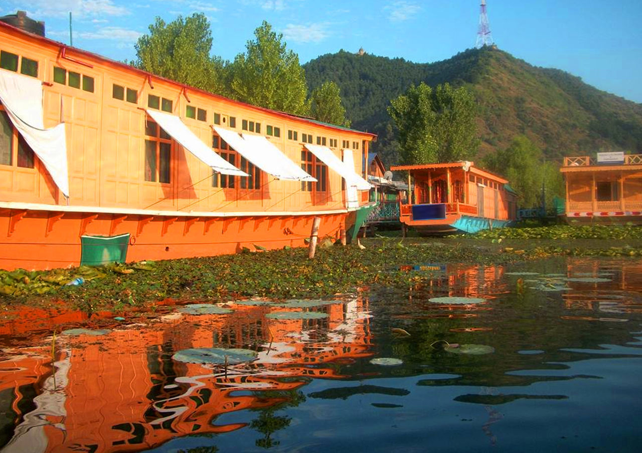 water, transportation, built structure, waterfront, architecture, day, outdoors, reflection, tree, mode of transport, nature, river, no people, houseboat, nautical vessel, mountain, sky, beauty in nature, building exterior
