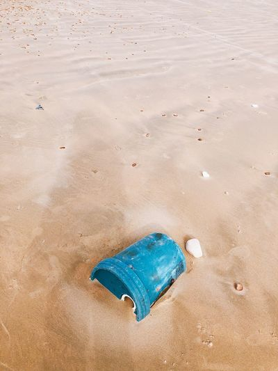 High angle view of blue plastic barrel on sand