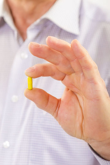 Midsection of man holding capsule