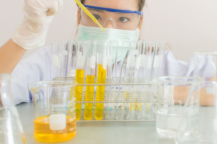 Close-up of scientist pouring liquid in test tube with pipette
