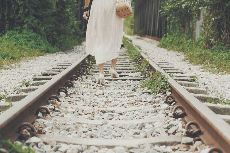 Woman Walking On Railroad Tracks