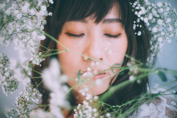 Close-Up Of Woman With Eyes Closed Wearing White Flowers