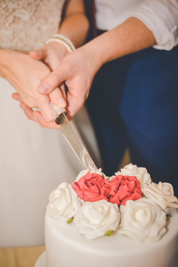 Midsection of bride and groom cutting wedding cake