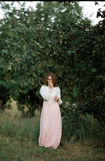 Portrait of woman biting fruit while standing against plant