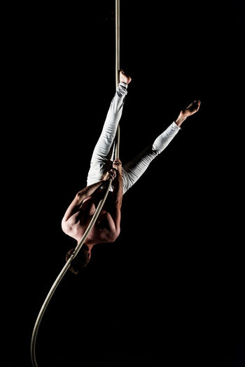 Young Man Doing Gymnastics Against Black Background