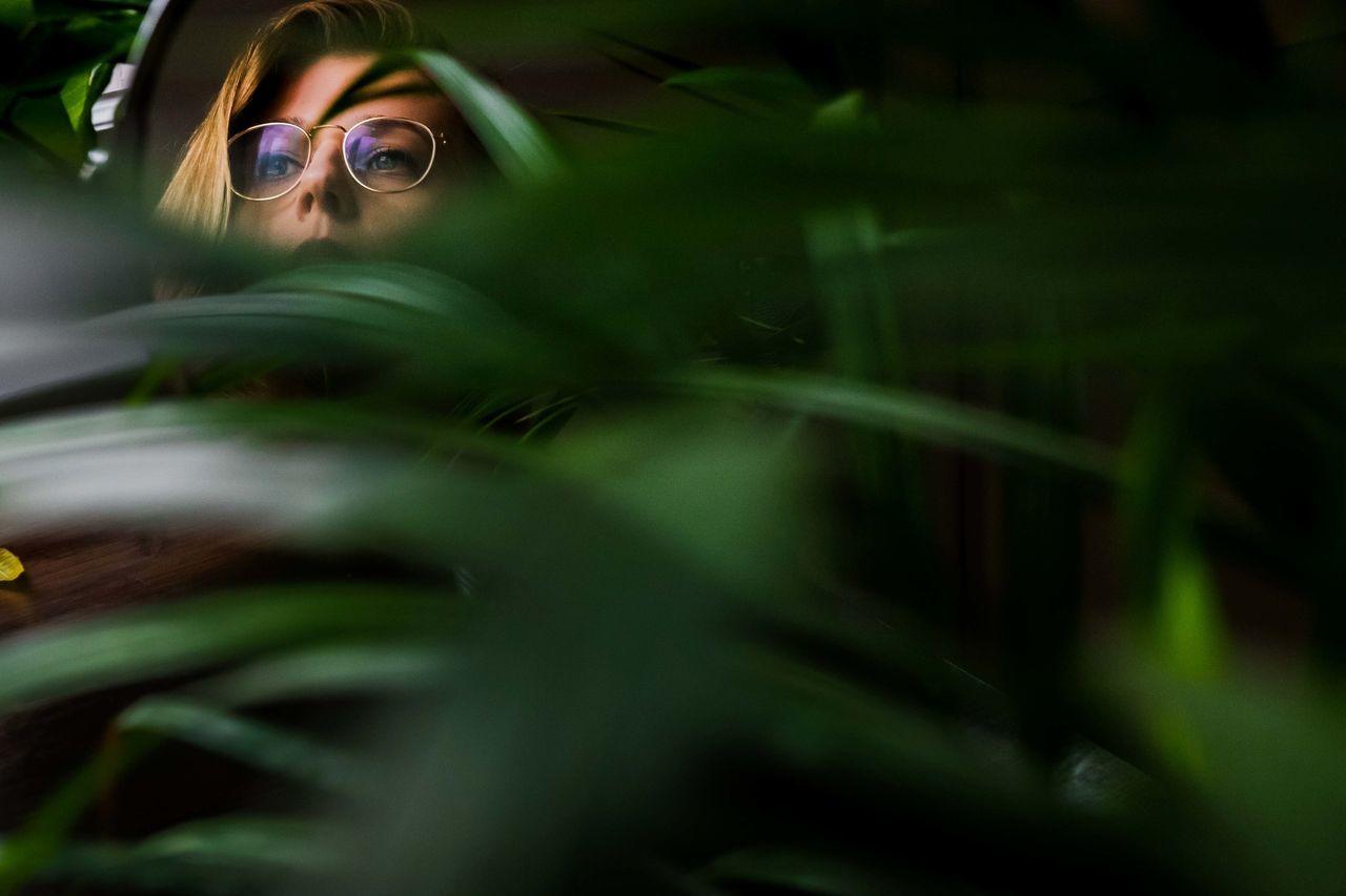 Thoughtful woman wearing eyeglasses seen through plants