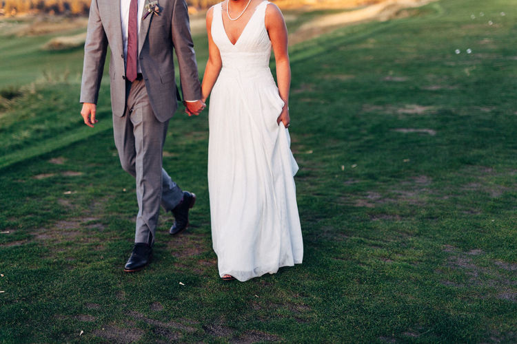 Low section of wedding couple holding hands while walking on field