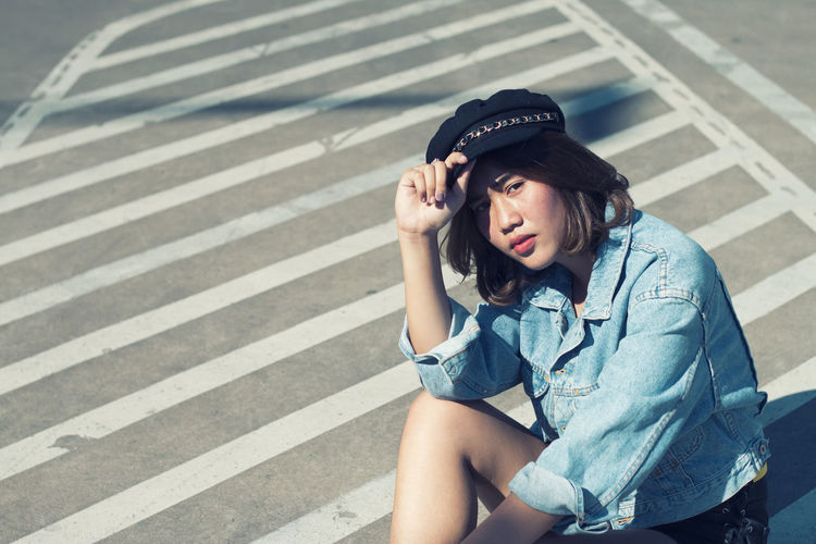 Portrait of young woman sitting on zebra crossing in city