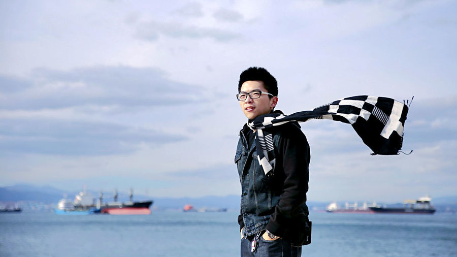 Smiling young man standing by sea against sky