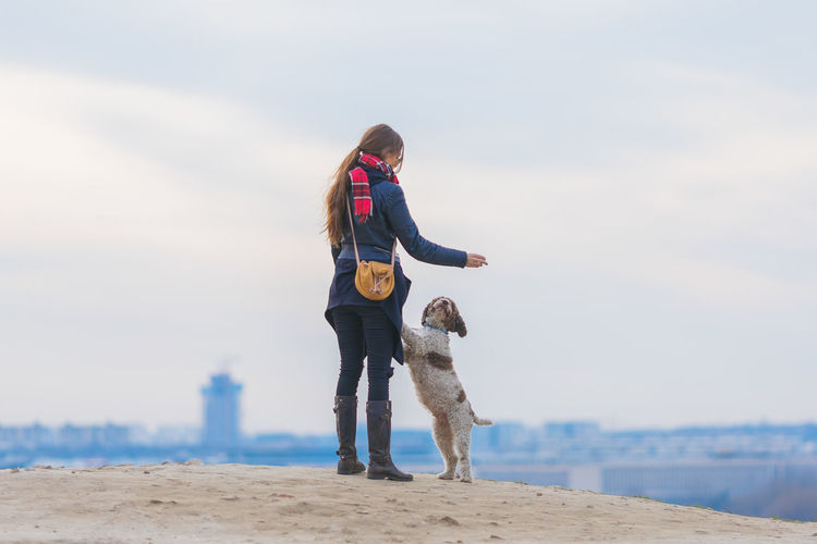 Woman standing with dog on hill against sky