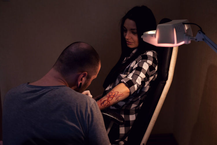 Woman is sitting on the chair and getting tattoo in tattoo salon Electric Lamp Son Shaved Head Communication Togetherness Waist Up Holding Technology Sitting Mid Adult Casual Clothing People Young Men Adult Young Adult Males  Lifestyles Real People Men Two People Indoors  Indoors  Males  Home Interior Connection Mid Adult Men Wireless Technology