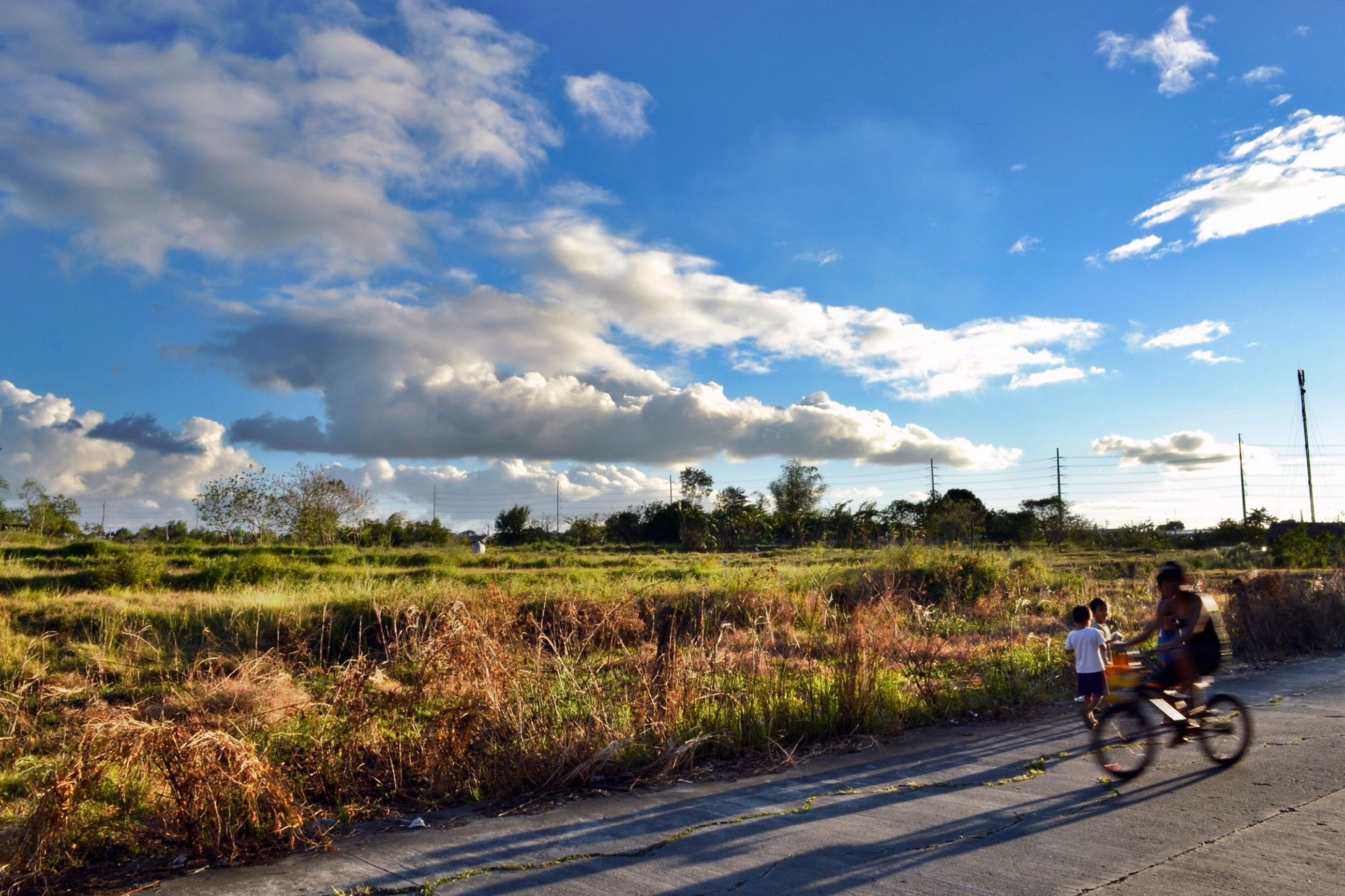 bicycle, transportation, land vehicle, mode of transport, riding, men, sky, lifestyles, leisure activity, cycling, full length, road, cloud - sky, motorcycle, travel, on the move, rear view