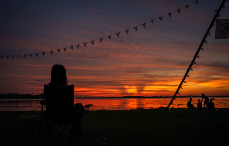 Silhouette people sitting on field against sky during sunset