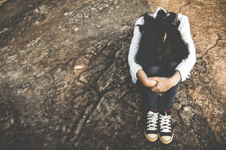 High Angle View Of Depressed Woman Sitting On Rock
