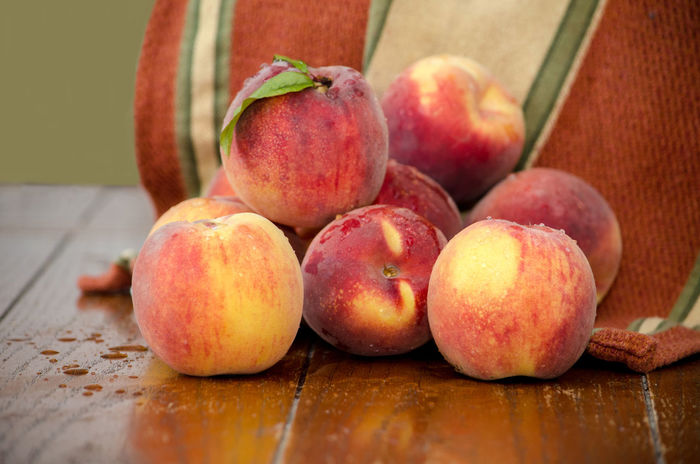 pile of sweet Michigan peaches on a wooden table Agriculture Fresh Produce Hello World Nature Orange Summertime USA Vitamins Fall Food Fresh Fruit Juicy Just Picked Michigan Peaches Natura' Organic Peach Peaches Produce Still Life Sweet Tasty Towel Yellow