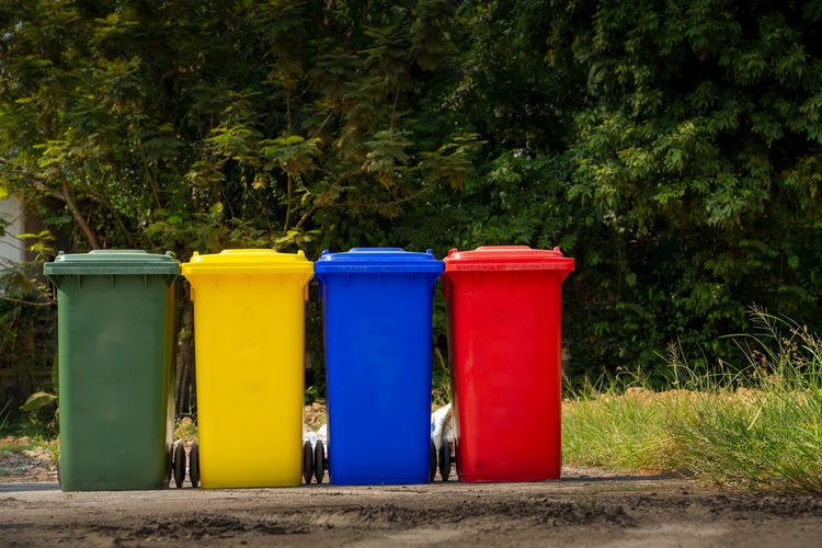 Multi colored garbage bins against trees