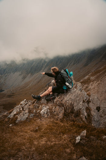 High angle view of man climbing on rock against sky