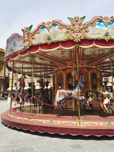 Carousel in amusement park against sky