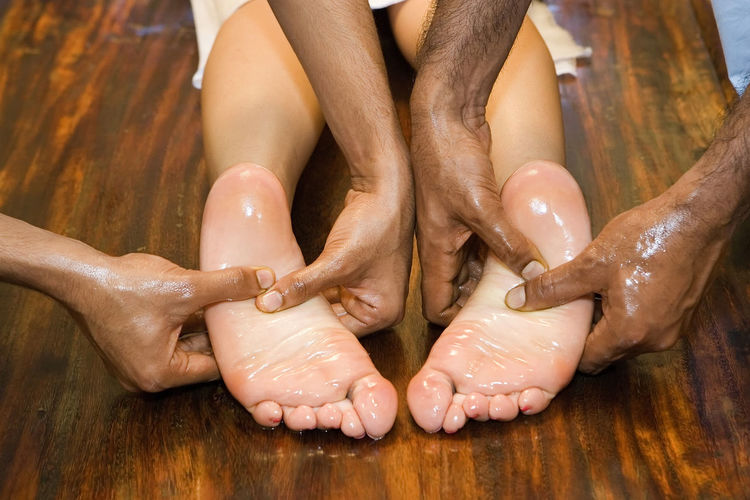 Cropped hands of men giving massage foot massage to woman at spa