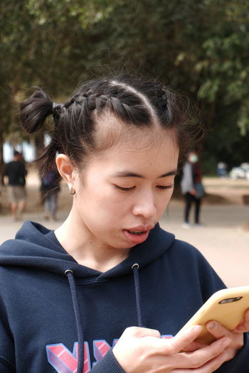 Close-up of young woman using smart phone in park