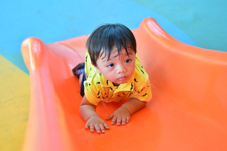 High angle view of cute boy looking away on slide