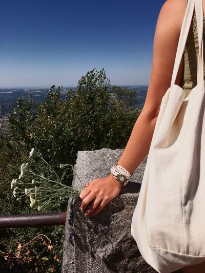Midsection of woman holding flowers while standing at observation point
