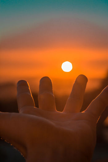 Close-up of hand against sun during sunset