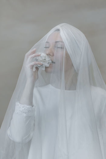 Midsection of woman wearing mask against white background