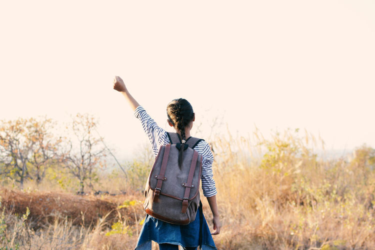 Rear view of girl with backpack standing on field against clear sky
