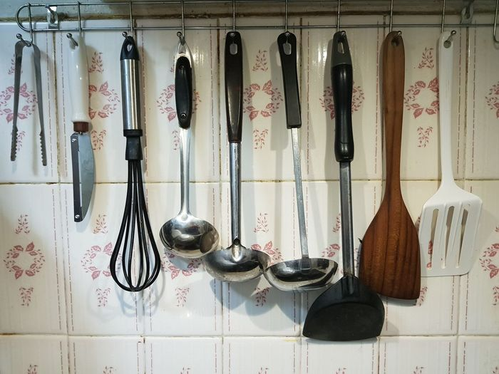 Close-Up Of Spatulas Hanging On Wall