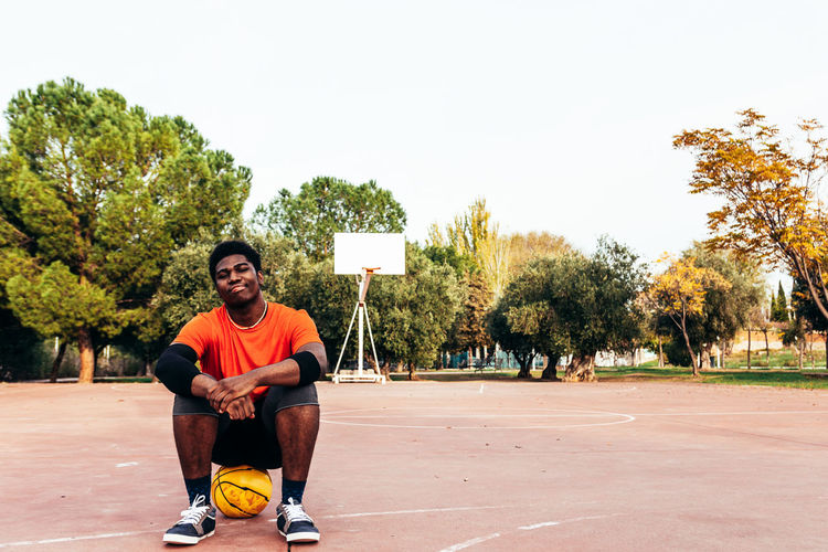 Portrait of young man sitting at basketball court