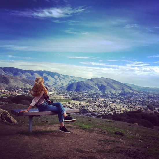 Woman sitting on bench with beautiful landscape in background