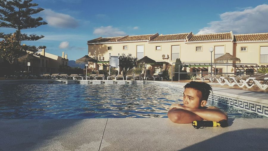 Man relaxing in swimming pool against cityscape