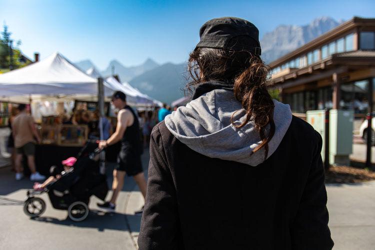 Rear view of woman in market against mountain range